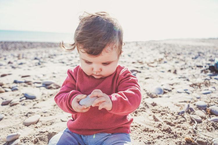 Full length of cute boy holding sand at beach