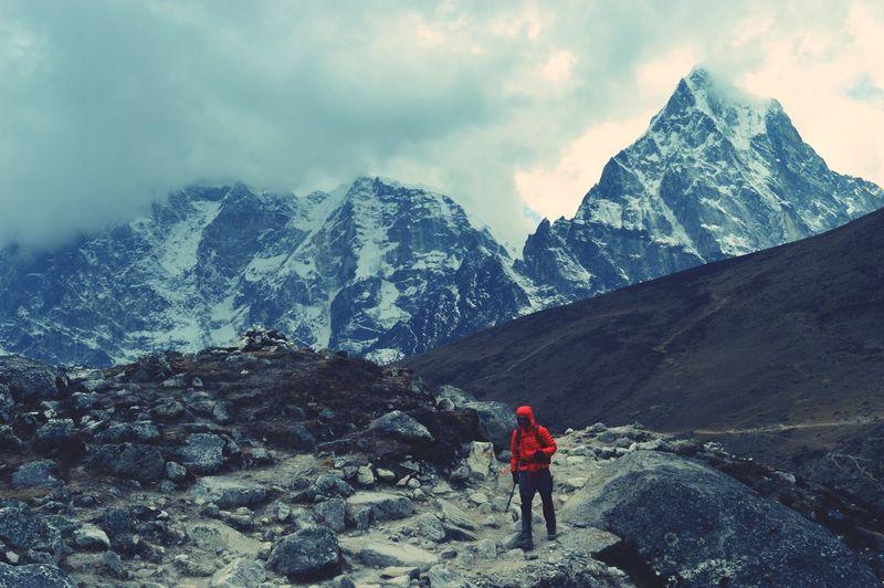 Full length of person trekking on snowcapped mountain against sky