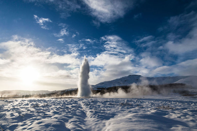 Geyser By Snow Field Against Sky