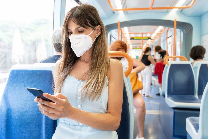 Woman wearing mask using smart phone sitting in bus