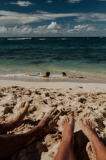 Low section of people relaxing on beach
