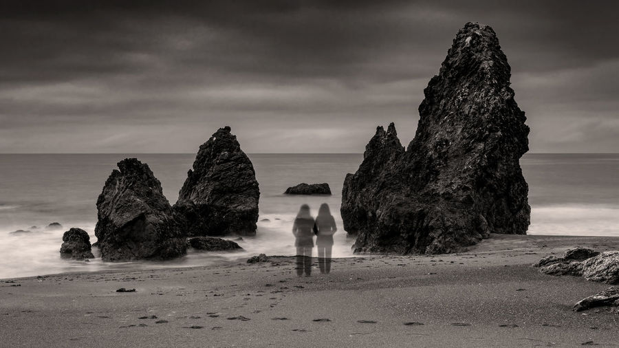 People standing on rock by sea against sky