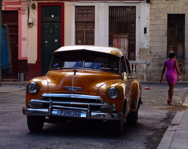 Woman Architecture Building Exterior Built Structure Car City Day Full Length Havana Street Land Vehicle Mode Of Transport Outdoors Purple & Orange Real People Street Transportation