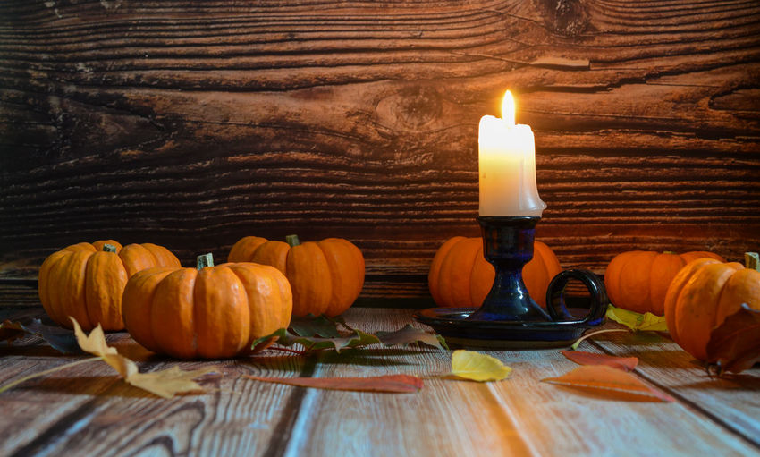 Lit candles on wooden table