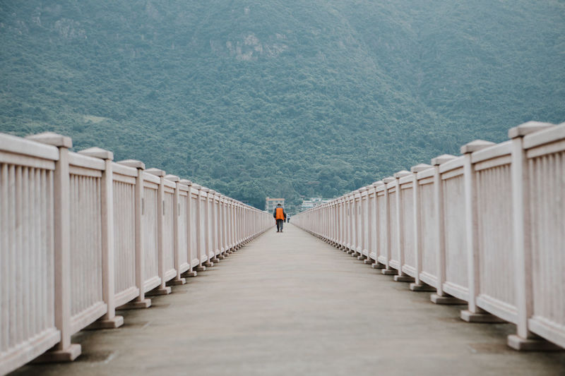 Man wearing orange jacket walking in center of bridge with a vanishing point