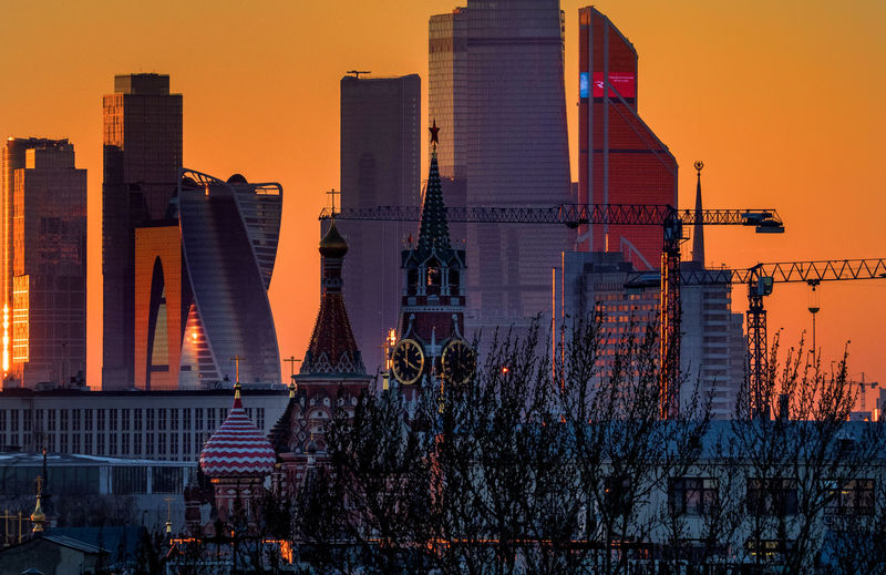 Spasskaya Tower And Skyscrapers In City Against Clear Sky During Sunset