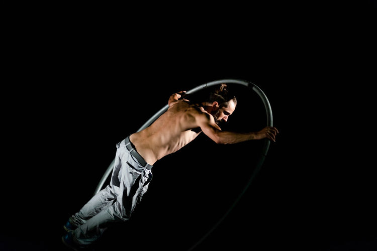 Circus Arts Culture And Entertainment Balance Black Background Concentration Copy Space Effort Exercising Flexibility Full Length Healthy Lifestyle Indoors  One Person Performance Shirtless Skill  Sport Sports Clothing Strength Studio Shot Young Adult