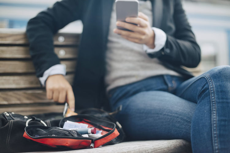 Midsection of man using mobile phone while sitting on bench
