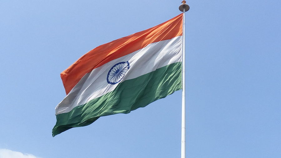 Low angle view of indian flag waving against clear sky