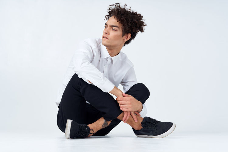 Young man looking away while sitting against white background
