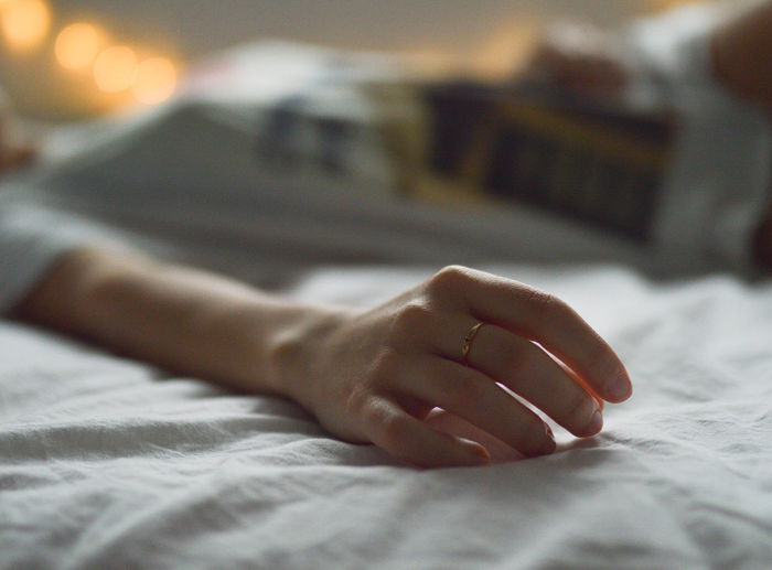 Close-Up Of Woman Hand Sleeping On Bed At Home