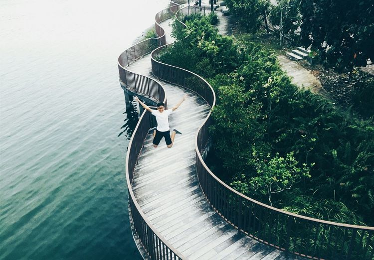 High Angle View Of Man Jumping On Boardwalk By River