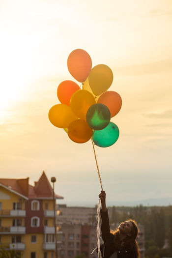 Woman holding multi colored balloons against sky during sunset