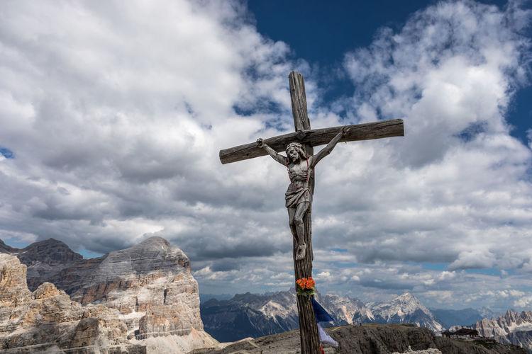 Crucifix against cloudy sky
