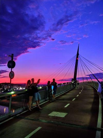 People on bridge against sky at sunset