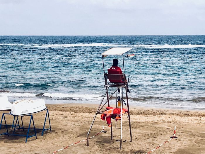 Rear view of chairs on beach against sky