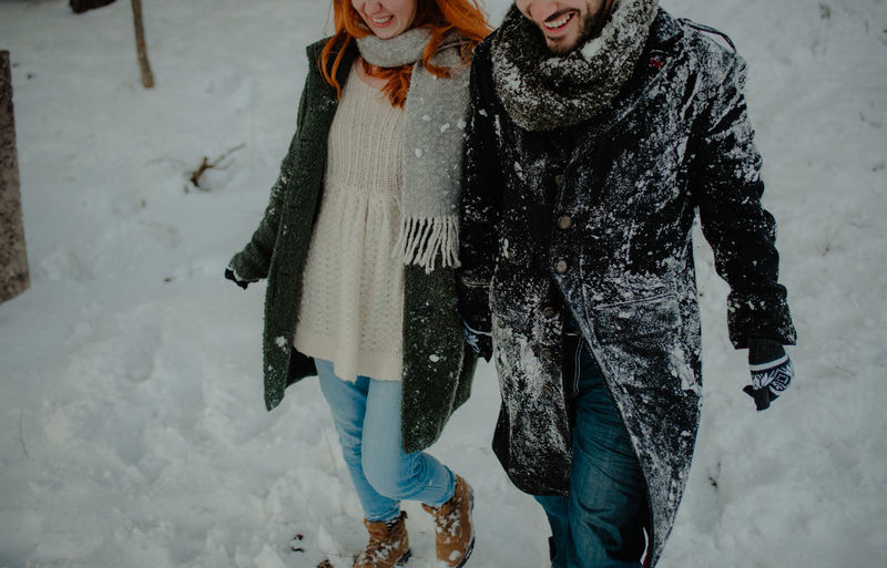 Midsection of couple holding hands walking on snow covered land in forest