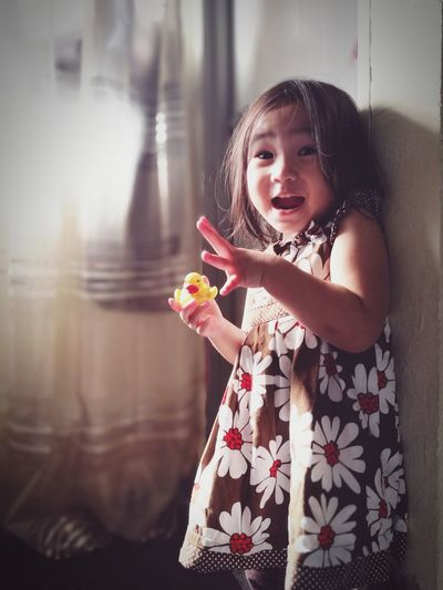 Portrait of shocked cute girl holding rubber duck