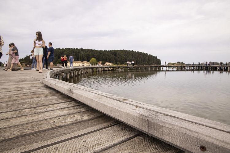 People on pier against sky