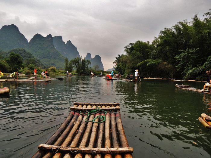 Wooden rafts in river against cloudy sky