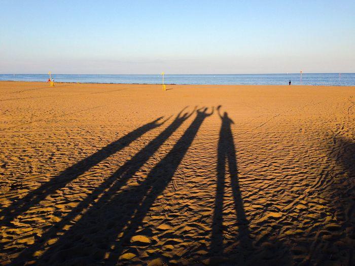 Long Shadows Of Friends At Sandy Beach Against Sky