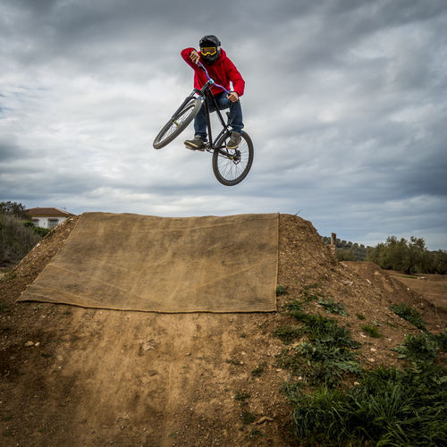 Low Angle View Of Man Jumping While Doing Bmx Cycling