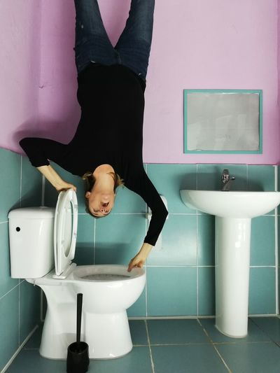 Woman upside down on toilet bowl in bathroom