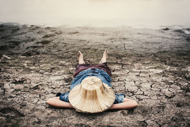 Girl lying down by pond on drought field