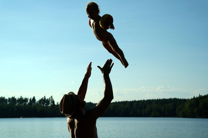 Man throwing girl while playing in lake against sky