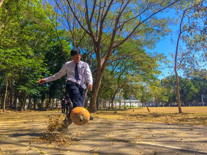 Full length of student kicking ball on street during autumn