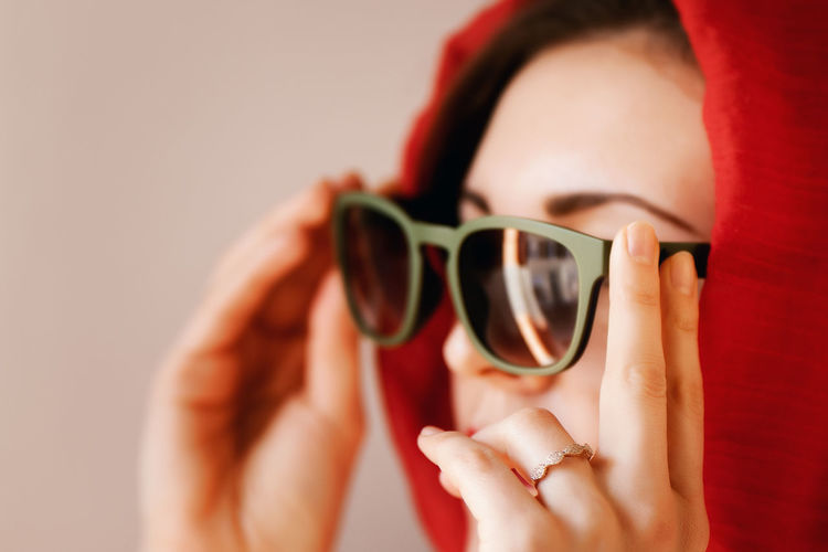 Close-up of woman holding sunglasses