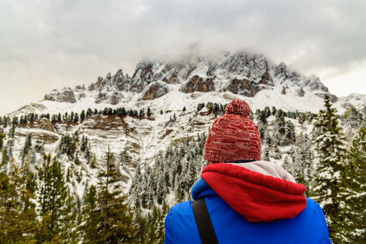 Rear View Of Person Looking At Snowcapped Mountain Against Cloudy Sky