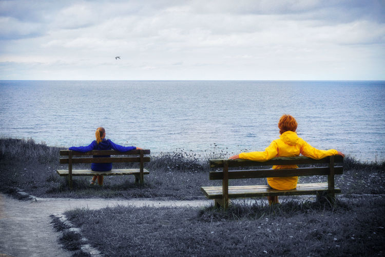 Rear view of people sitting on bench by sea against sky