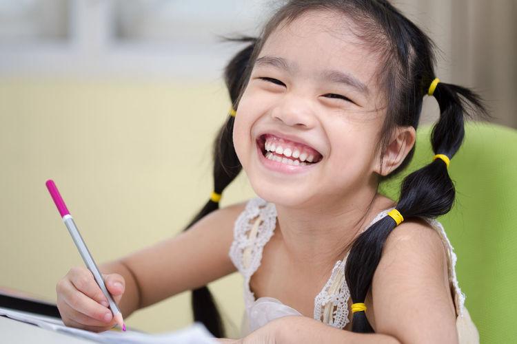 Close-Up Of Cheerful Girl Writing At Home