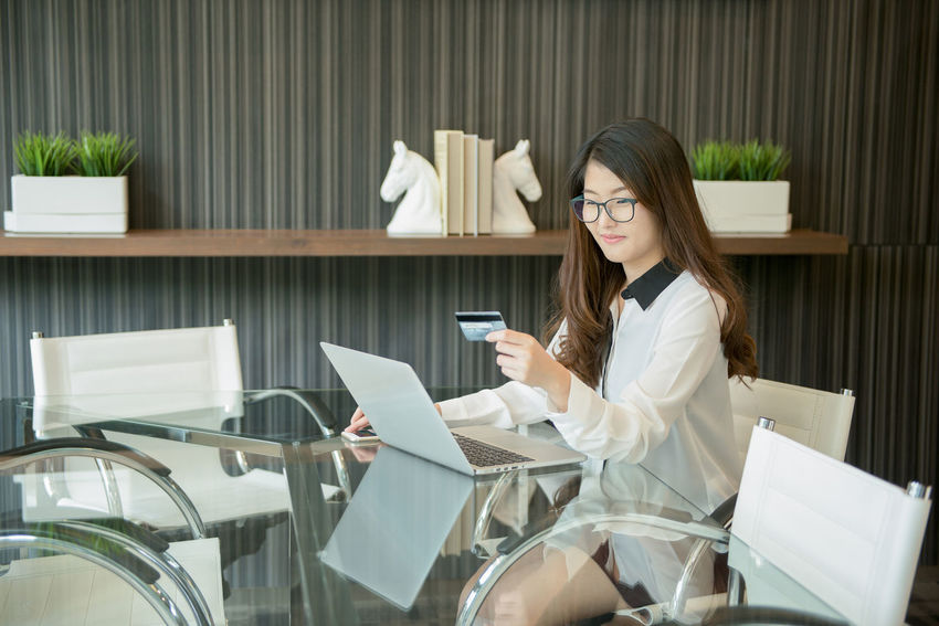 An Asian business woman using a credit card in front of a laptop Office Working Business Business Woman Communication Computer Day Eyeglasses  Holding Indoors  Internet Laptop Lifestyles Meeting Room Occupation One Person Portable Information Device Real People Sitting Technology Using Laptop Wireless Technology Women Working Young Adult Young Women