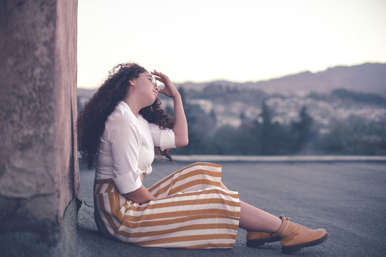 Young woman with curly sitting outdoors