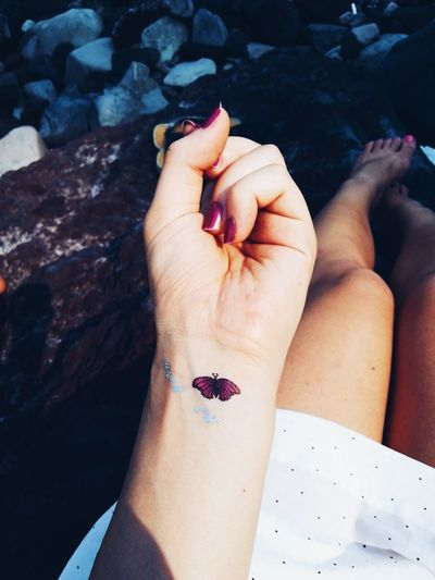 Cropped image of woman showing butterfly tattoo