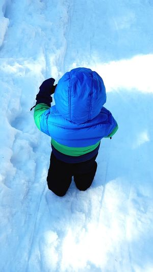 Rear view of man in snow against sky
