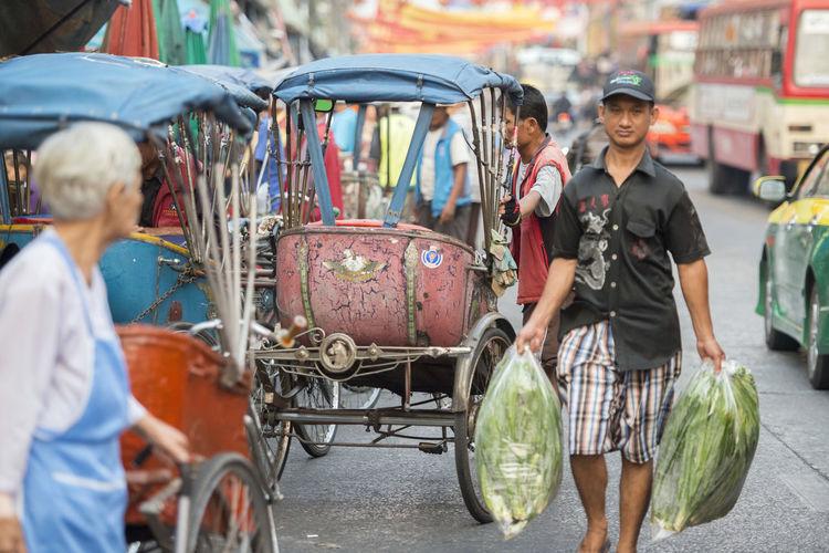 People walking by jinrikishas on street in city