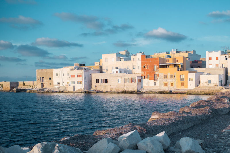 Buildings in city by sea against sky