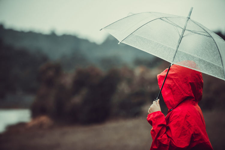 Midsection of person holding umbrella during rainy season
