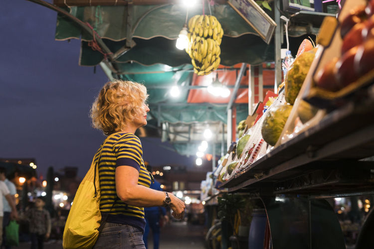 Rear view of woman standing at illuminated market