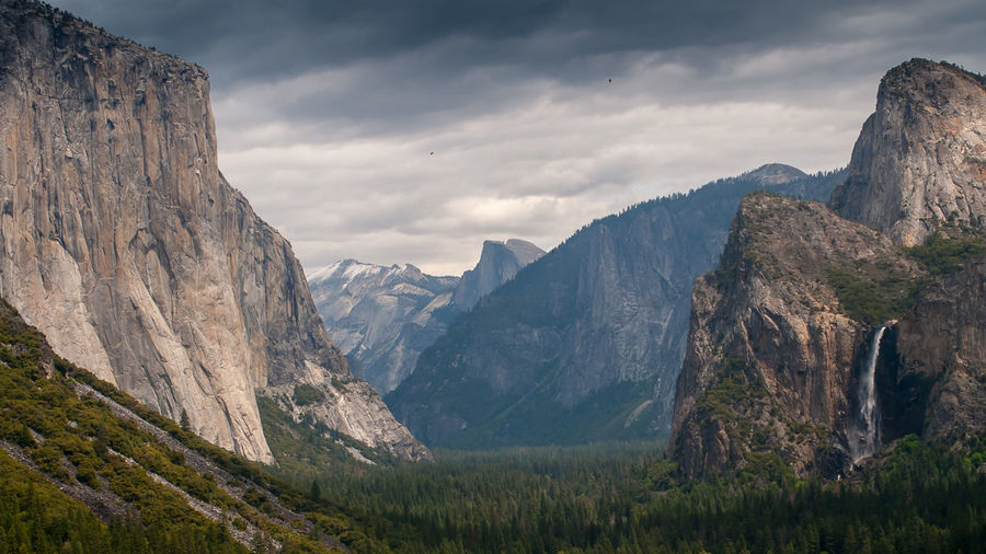 Rocky mountains by grassy field against cloudy sky at yosemite national park