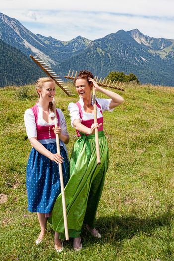Two bavarian women in dirndl with rakes on their shoulders having fun in a meadow in the mountains Agriculture Bavaria Field Work Work Adult Cheerful Dairymaids Day Dirndl Full Length Grass Happiness Healthy Lifestyle Lifestyles Mountain Mountain Farmers Mountain Range Nature Outdoors Rakes Smiling Standing Togetherness Two People Women