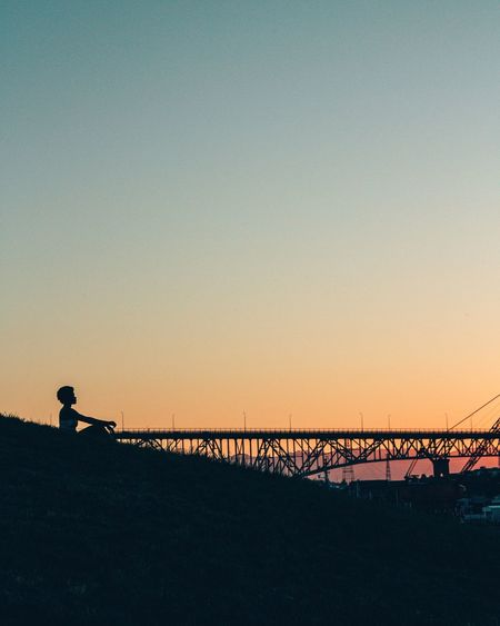 Silhouette Woman Sitting By Bridge Against Sky During Sunset