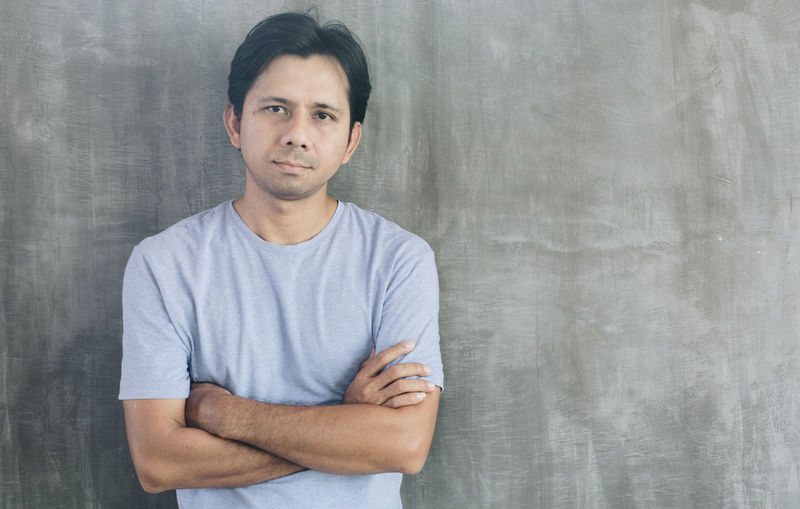 Portrait of man standing against white background