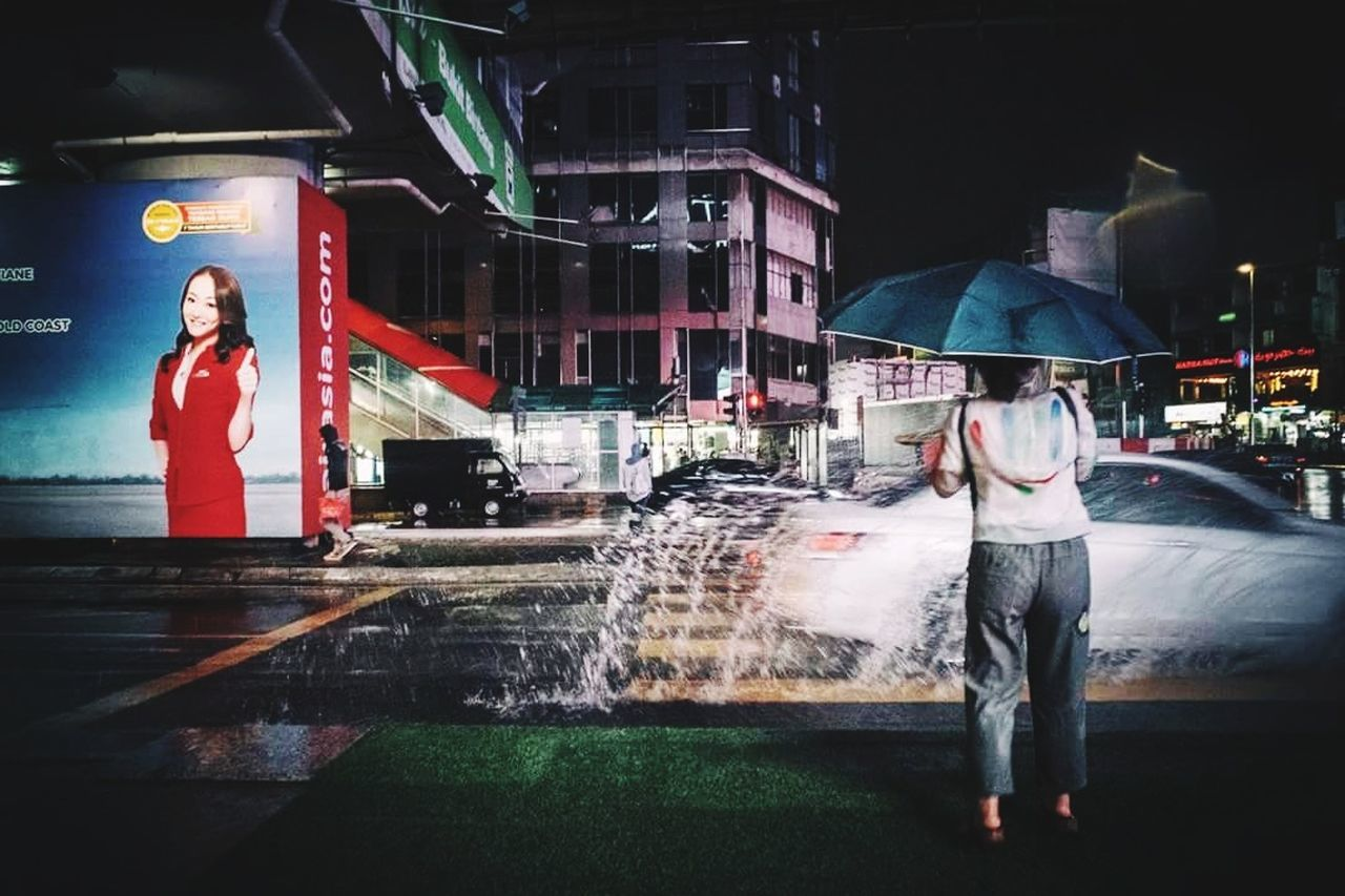 real people, water, two people, motion, leisure activity, lifestyles, wet, protection, night, full length, illuminated, long exposure, outdoors, architecture, standing, women, building exterior, spraying, built structure, men, city, under, young adult, adult, people