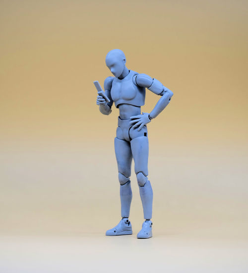 A grey man doll holding a mobile phone standing at yellow background. Dog Dolls Full Length Futuristic Green Color Grey Hand Phone Men Mobile Conversations Model One Person People Standing Studio Shot Young Adult