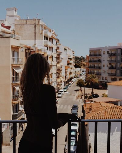 Rear View Of Silhouette Woman Standing In Balcony Against Buildings In City
