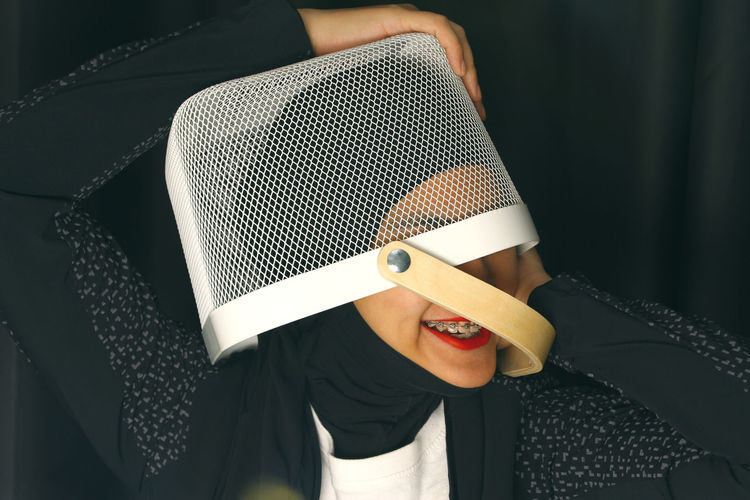 Young woman in hijab with basket on head against black background